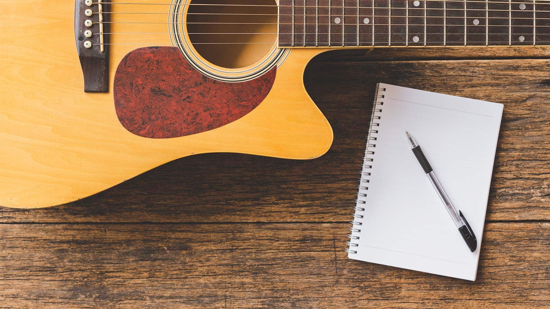 Guitar and pad of paper on wood table