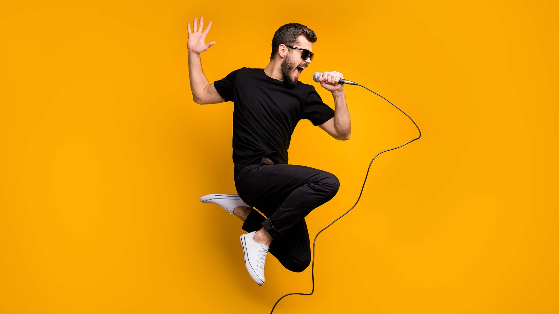 Man jumping in air with microphone and sunglasses on yellow background